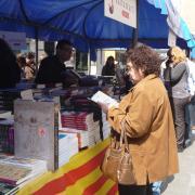 Persones que remenen i compren llibres a la plaça de la Vila a Badalona