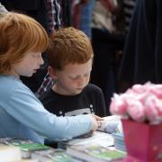 Dos nenes remenen llibres en una de les parades de la Rambla Catalunya de Barcelona