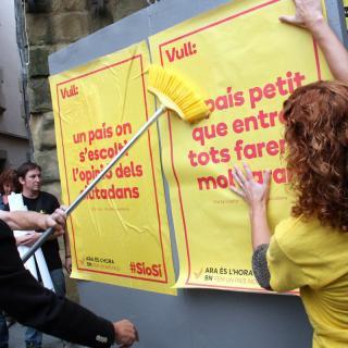 Enganxada del primer cartell de la campanya a Vic