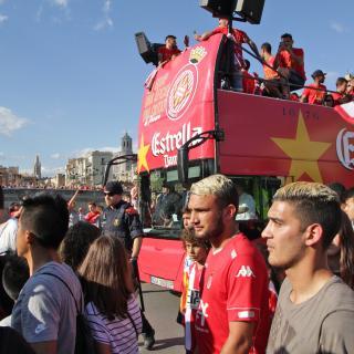 Els jugadors dalt de l'autocar travessant la Plaça de Catalunya de Girona