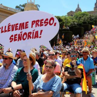 Una assistent amb una pancarta reivindicativa del referèndum i de desafiament als estaments judicials espanyols