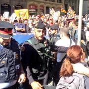 Un mosso d'esquadra amb un clavell al pit durant les protestes ciutadanes a Barcelona