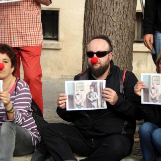 Persones assegudes davant la fiscalia de Tarragona amb nas de pallasso i cartells amb la imatge de Jordi Pesarrodona al costat d'un guàrdia civil