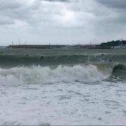 Desenes de persones aprofitant la llevantada per sortir a fer surf, a l'Escala