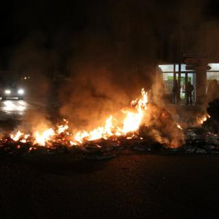 Un vehicle intentant passar entre la crema de pneumàtics i bales a l'N-II a Bàscara