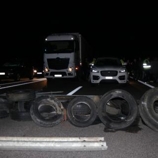 Una filera de pneumàtics a l'AP-7 a l'Ampolla, davant de diversos camions