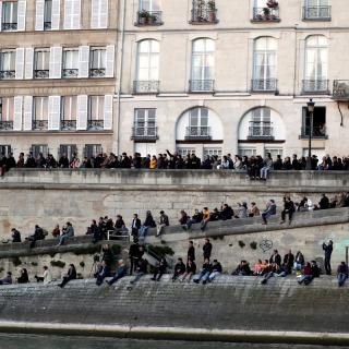 Desenes de persones miren l'incendi a Notre-Dame des del costat del riu Sena
