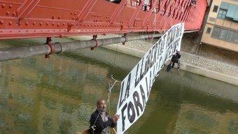 Els manifestants penjats i desplegant una pancarta. Foto:JORDI CAMPS