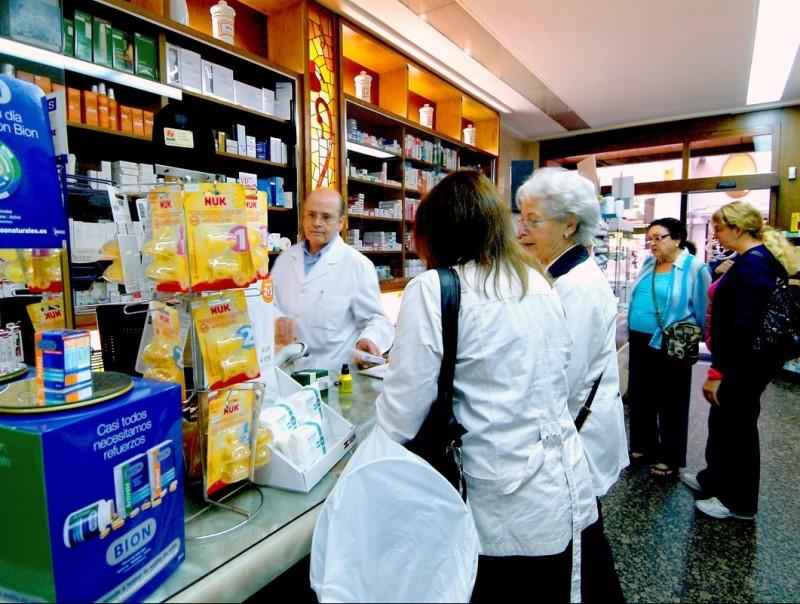 Un grup de gent espera en una oficina de farmàcia per comprar
