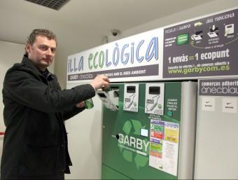 Jordi Pita diposita un envàs a una de les màquines compactadores.  Foto:JUDIT FERNÀNDEZ