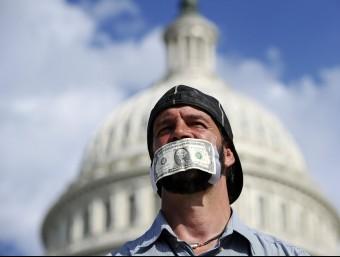 Un manifestant davant el Congrés dels EUA, reclamant amb un dòlar a la boca un acord sobre el pressupost.  Foto:AFP