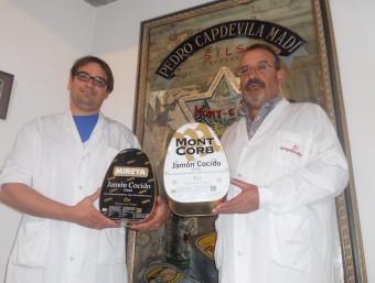 Marc Capdevila i Pere Capdevila, amb dues de les llaunes típiques del seu pernil més popular.  Foto:URE COMAS