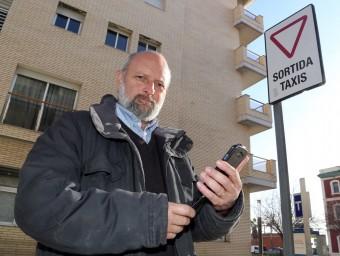 José Franco amb el seu telèfon intel·ligent en una parada de taxis davant l'estació de trens de Mataró.  Foto:QUIM PUIG