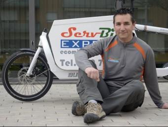 Joan Admetlla, amb la bicicleta que utilitza per fer el transport de paquets.  Foto:JUDIT TORRES