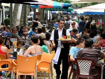 Un cambrer en una terrassa a Blanes Foto:MANEL LLADÓ/ARXIU