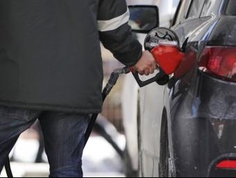 Un home posa gasolina al seu cotxe.