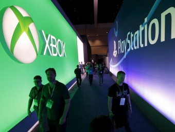 Attendees walk between Microsoft and Sony logos at E3 in Los Angeles.  Foto:REUTERS/LUCY NICHOLSON