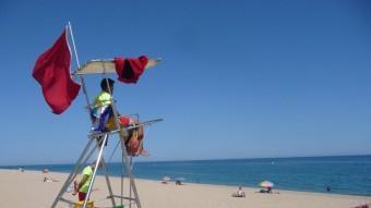 Dos socorristes a la platja de Pineda amb la bandera vermella que prohibeix el bany ahir a la tarda. Foto:T.M