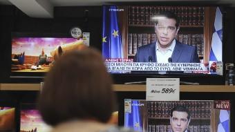 Una dona observa ahir, a Atenes, el discurs televisat de Tsipras Fotis Plegas A. / EFE