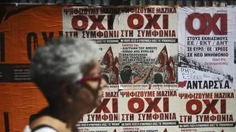 Una dona, passant per davant d'uns cartells que demanen el no en el referèndum de diumenge vinent, ahir, a Atenes Foto:EFE