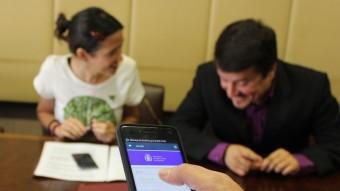 L'aplicació del mòbil per pagar amb el nou sistema, amb Núria Parlon i Jaume Catarineu, al fons Foto:EL PUNT AVUI