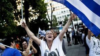 Una dona, celebrant la victòria del no en el referèndum d'ahir a Grècia, a la plaça Syntagma d'Atenes Angelos Tzortzinis / AFP