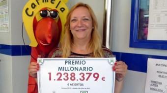 Maria Àngels Vallès , treballadora de l'administració Carmela, amb el cartell del premi de la Bonoloto Foto:RÀDIO PALAMÓS