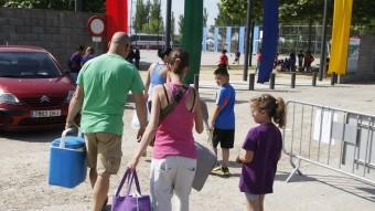 Una parella amb dos fills carregats amb bosses i nevera Foto:ORIOL DURAN
