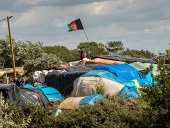 Una bandera afganesa, damunt d'un campament d'immigrants sense papers prop de Calais. Els immigrants intenten entrar a l'Eurotunnel. Foto:P. HUGUEN/AFP