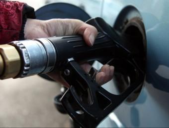 Una mà subjecta la mànega d'un assortidor de gasolina.