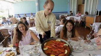 Un cambrer mostra una paella en un restaurant de València. Foto:EL PUNT AVUI