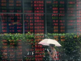 Una dona, passant pel davant d'una finestra amb dades borsàries reflectides en ella, ahir, a Xangai Foto:REUTERS