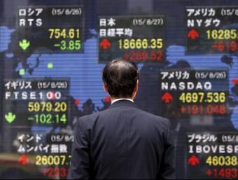Un home mira una pantalla amb l'evolució a la Borsa de Tòquio Foto:REUTERS