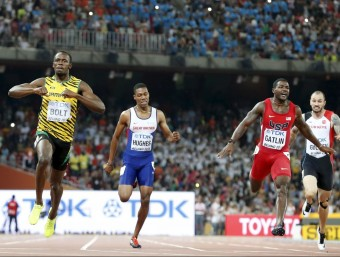 Bolt assenyala el seu dorsal a l'arribada dels 200 m per evidenciar el seu lideratge mundial Foto:REUTERS