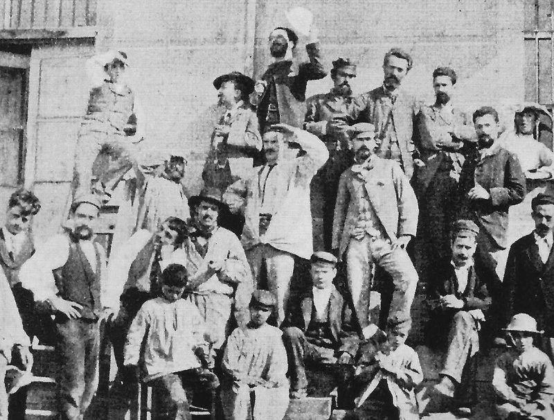 Imatge de Marian Vayreda a la fila de dalt, aixecant un barret blanc, amb els socis i empleats de l'Art Cristià.