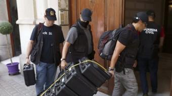 Agents de la Guàrdia Civil i Anticorrupció traslladen maletes per procedir a l'escorcoll de la fundació Catdem Foto:EFE
