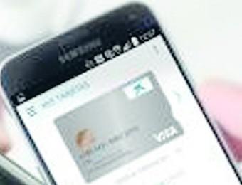 Un mòbil amb l'aplicació de CaixaBank, junt amb un datàfon 'contactless' Foto:EL PUNT AVUI