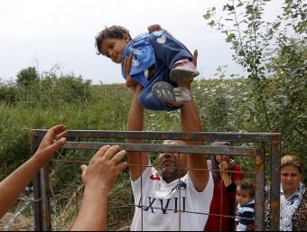 Una família passa un nen per sobre la tanca que separa la frontera entre Sèrbia i Hongria Foto:REUTERS