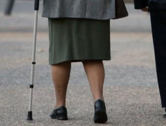Una pensionista amb problemes de mobilitat passeja amb l'ajut d'una crossa Foto:MANEL LLADÓ / ARXIU