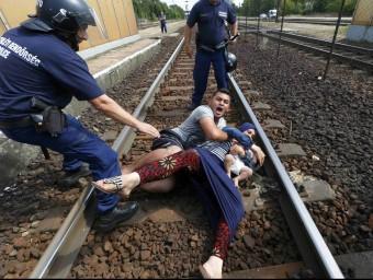 La policia intenta treure de la via del tren una família amb un bebè que protesta per poder pujar en un comboi, prop de la ciutat hongaresa de Bicske Foto:REUTERS