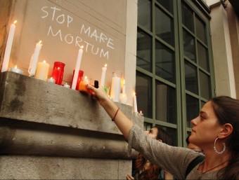 Una noia col·loca una espelma davant d'una pintada on es llegeix Stop Mare Mortum Foto:ACN