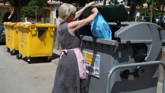 Una veïna de Torroella llençant la brossa en un contenidor del municipi, en una imatge d'arxiu Foto:LL. SERRAT