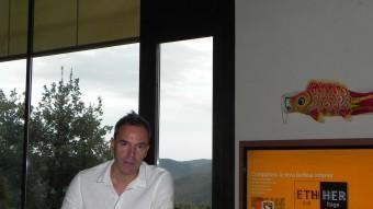 L'olotí Jordi Bartrina, fotografiat a casa seva amb la pàgina d'inici del seu web Ethical Heritage de teló de fons. Foto:J.C