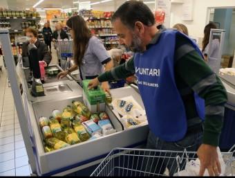Un voluntari , en un supermercat de Girona, en la campanya de l'any passat. Foto:MANEL LLADÓ