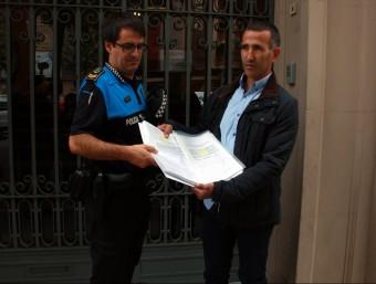 L'alcalde d'Alcarràs, Miquel Serra i el sergent de la policia local del municipi lliurant les signatures Foto:ACN