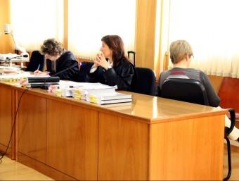 L'acusada, Remei Barrera, asseguda d'esquenes al costat de la seva advocada al banc dels acusats de l'Audiència de Tarragona Foto:ACN
