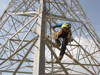 Dos operaris treballant en una de les torres d'alta tensió Foto:XAVIER PI