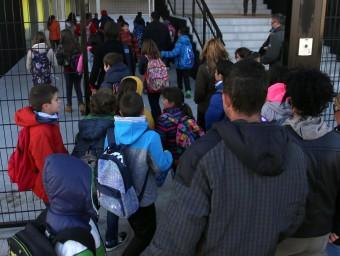Una imatge d'alumnes i familiars, entrant per primer cop a la nova escola, ahir al matí Foto:QUIM PUIG