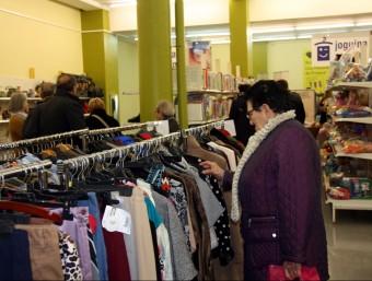 Una dona que mira la roba de segona mà a la nova botiga Troballes de Càritas a Lleida Foto:ACN
