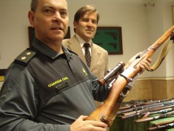 El tinent coronel Jorge Cumba empunya una de les armes davant del subdelegat Juan Manuel Sánchez Bustamante i dertall d'alguna de les 217 armes comissades a Camprodon. Foto:TURA SOLER